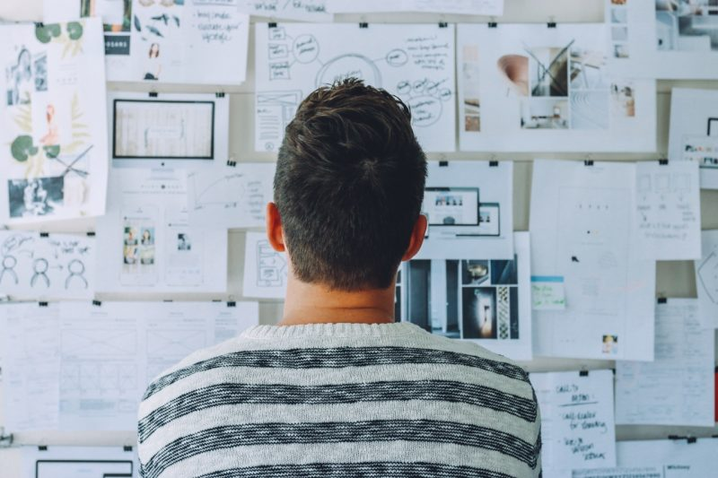 man looking at ideas board