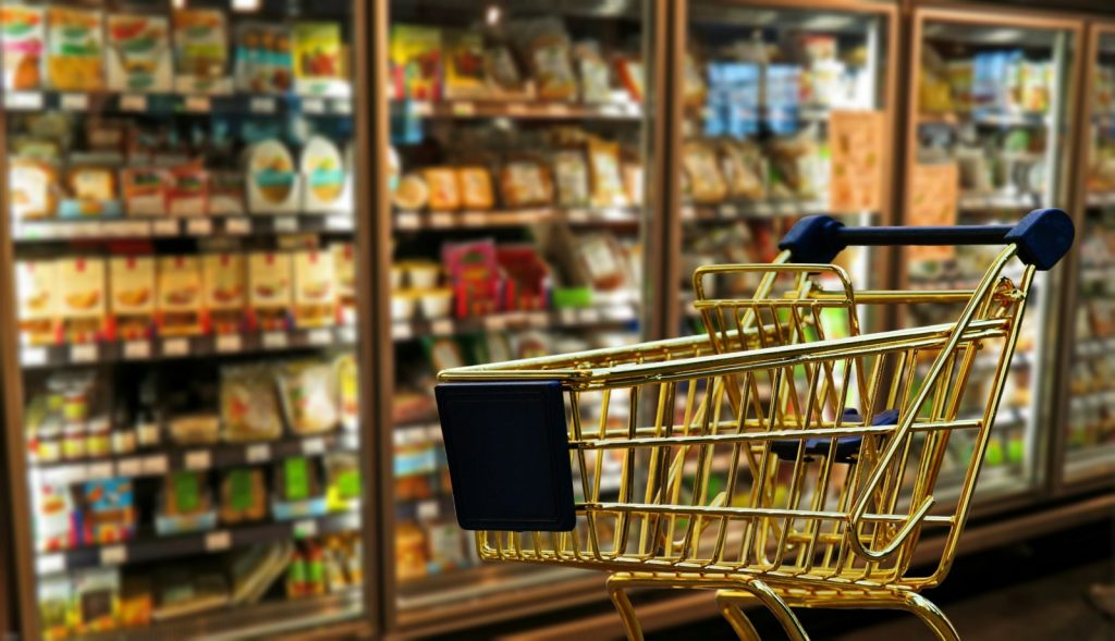 Shopping trolley in front of fridge aisle