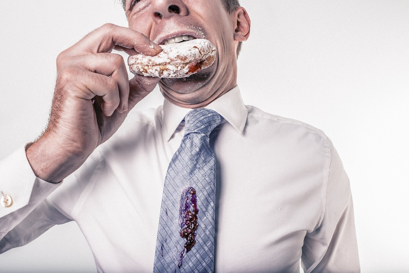 A business man eating a donut spills jam on his tie